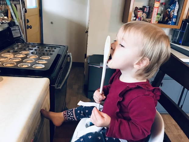 Toddler licking spoon while baking muffins