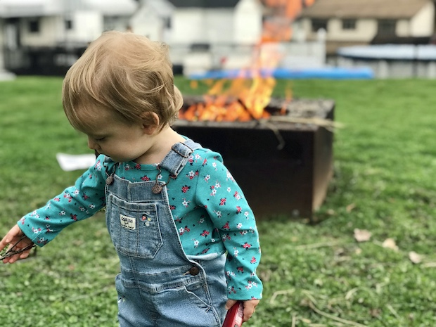 Toddler in overalls by bonfire