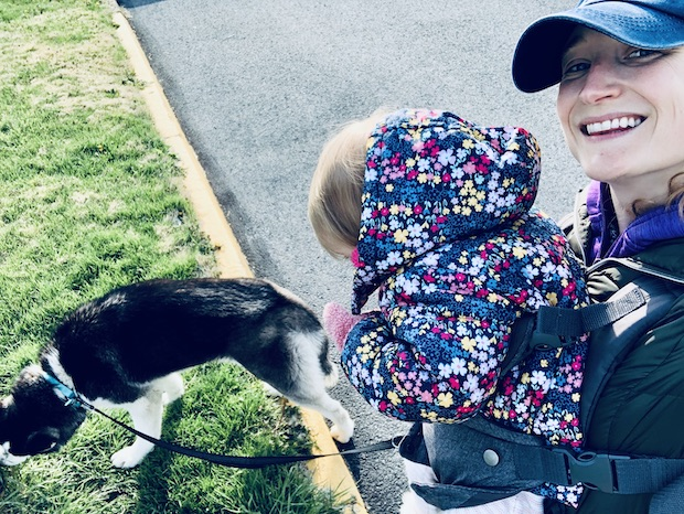 Husky and baby in carrier on walk