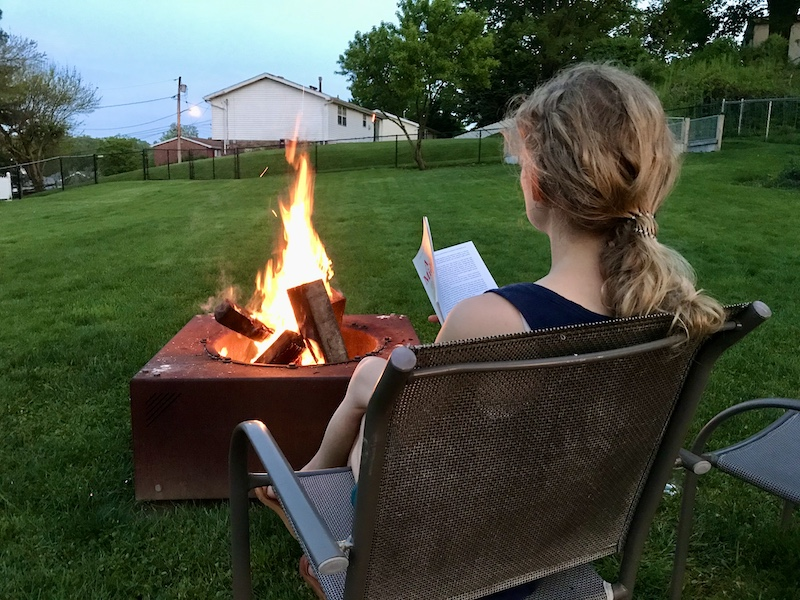 Girl reading book by fire