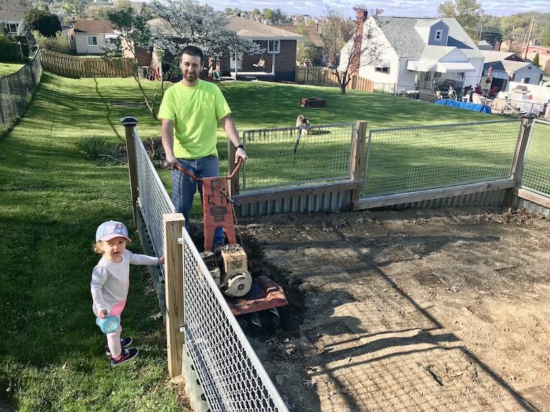 Dad and daughter tilling garden