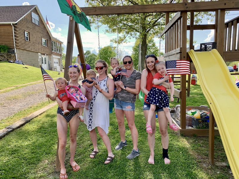 Moms with their daughters on Memorial Day holding flags