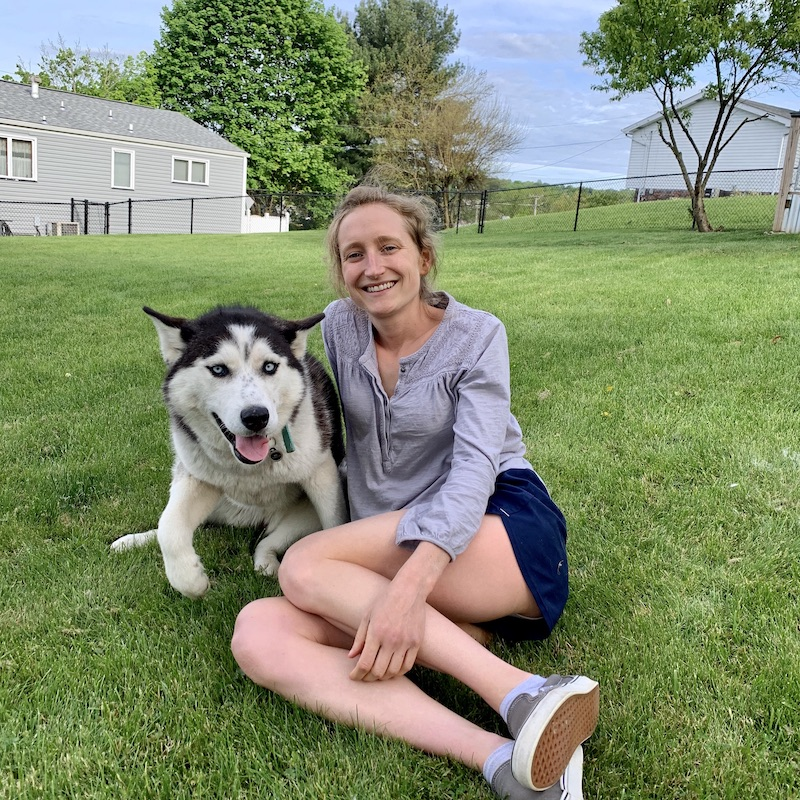 Husky and girl sitting in grass