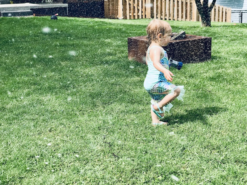 Toddler playing in sprinkler