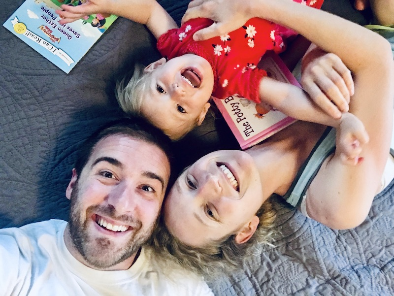 Family laying on bed smiling