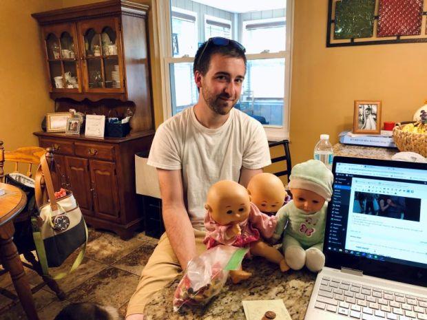 Guy sitting with three baby dolls