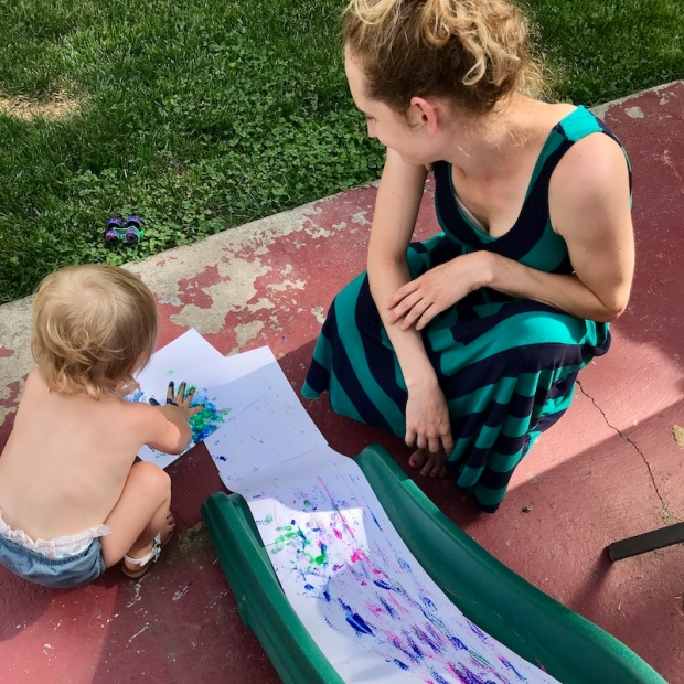 Toddler playing with paint on slide