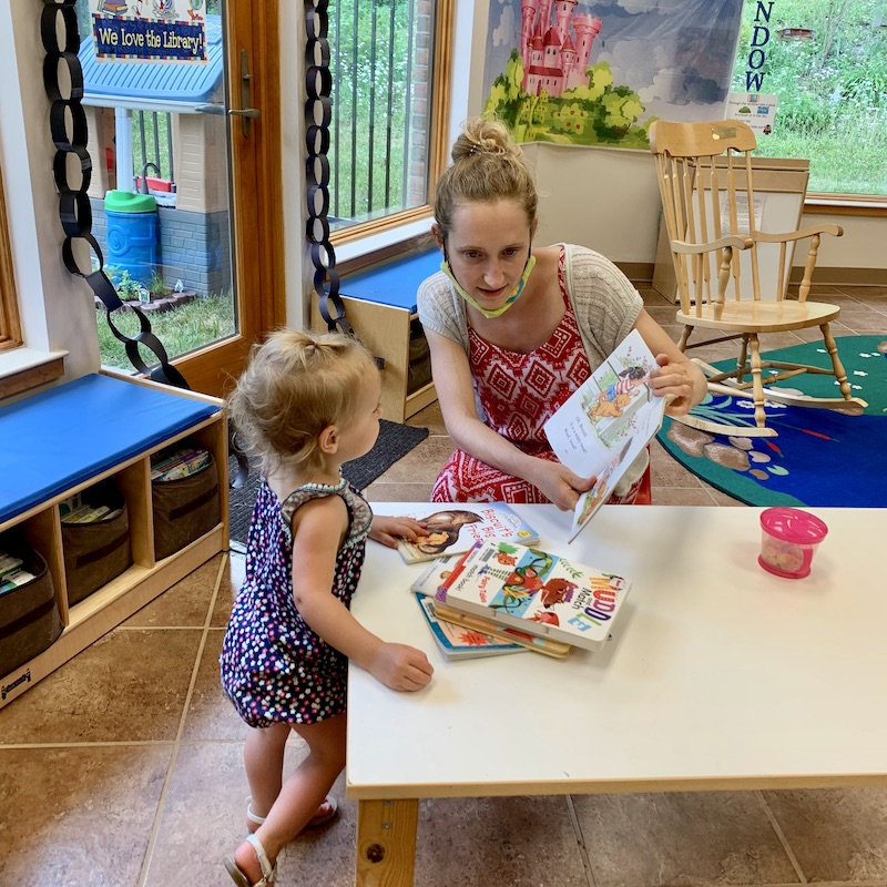 Mom and daughter reading at library