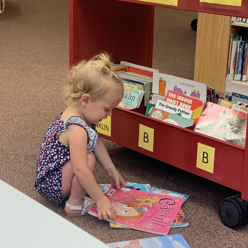 Toddler reading books at library