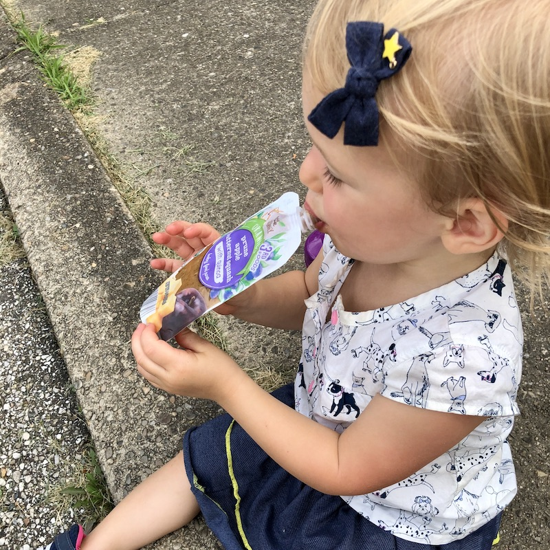 Toddler eating baby food pouch from Aldi