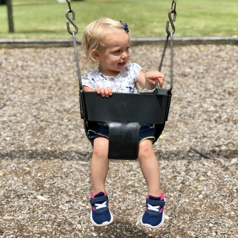 Toddler in swing at park