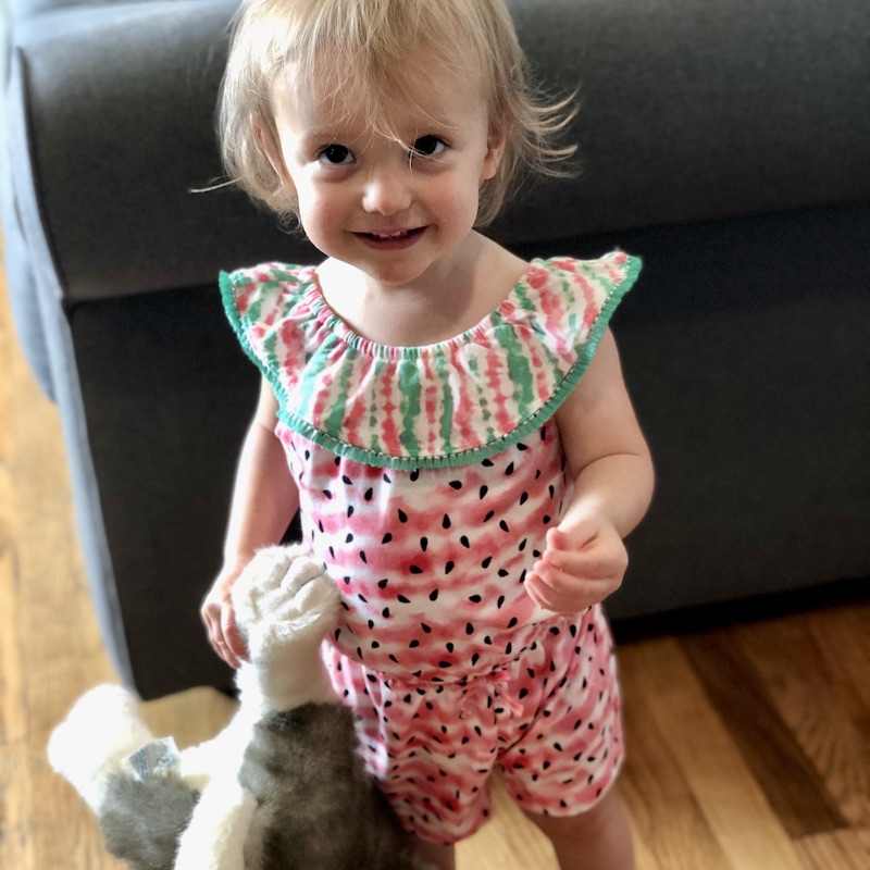 Toddler in watermelon romper with husky stuffed animal
