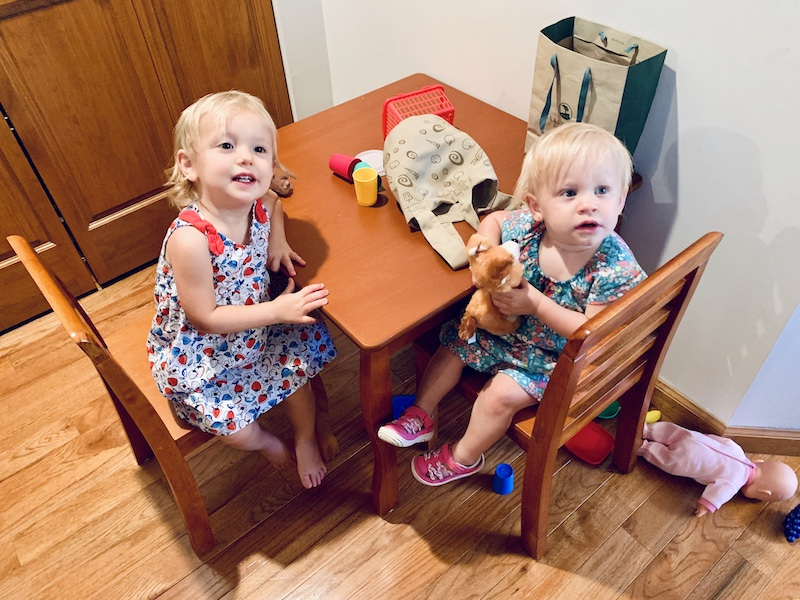 Toddler girls sitting at kid table with food toys
