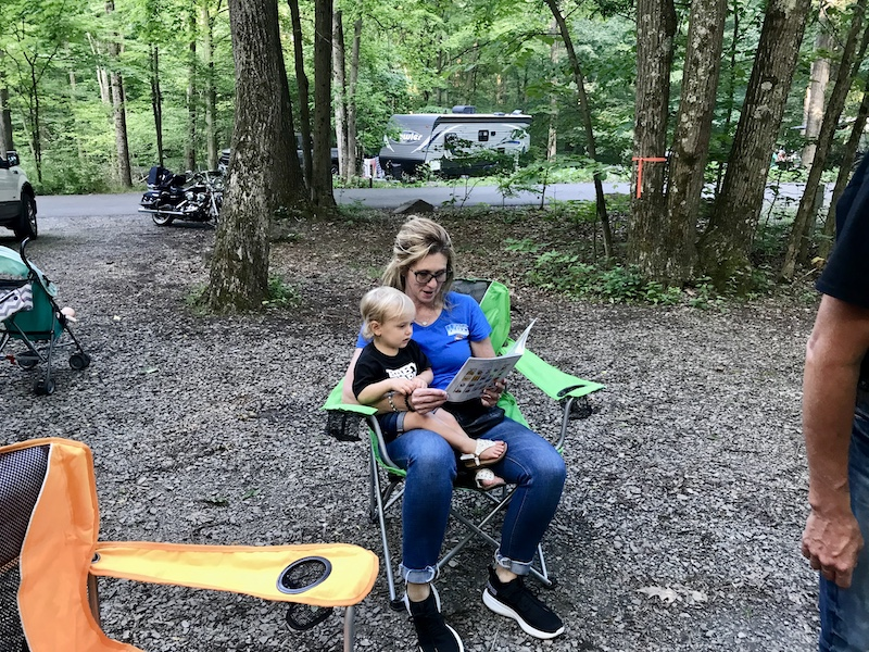Toddler and Grandma reading books while camping