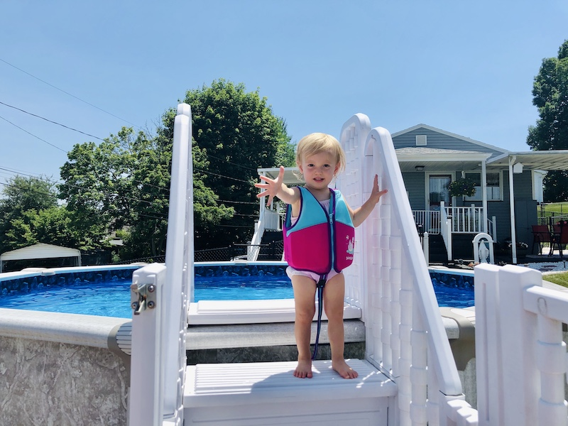 Toddler in life jacket by pool