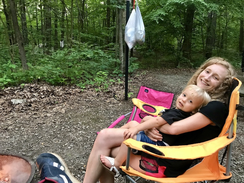 Mom and toddler sitting in camp chairs by campfire while camping