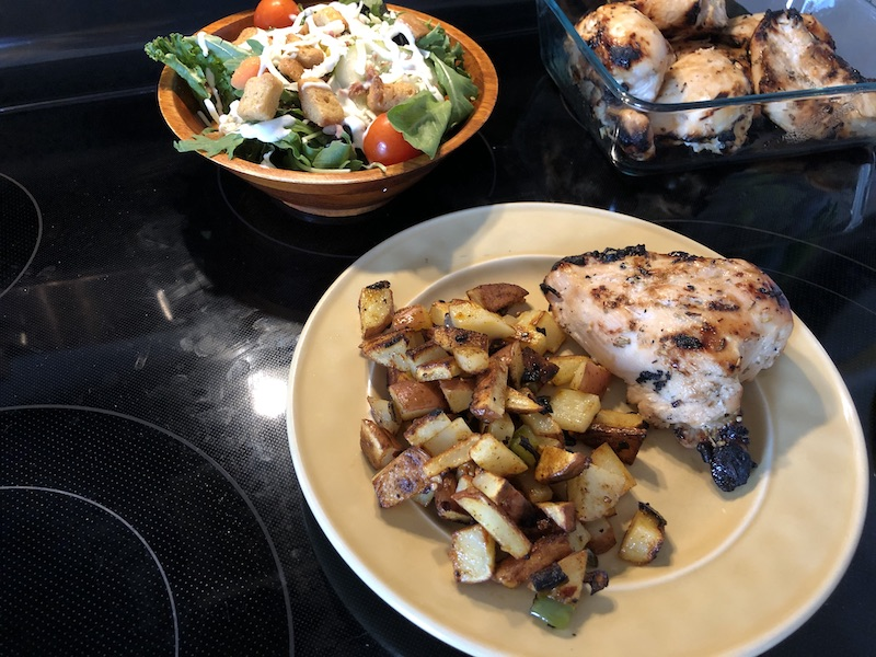 Chicken, fried potatoes, and salad