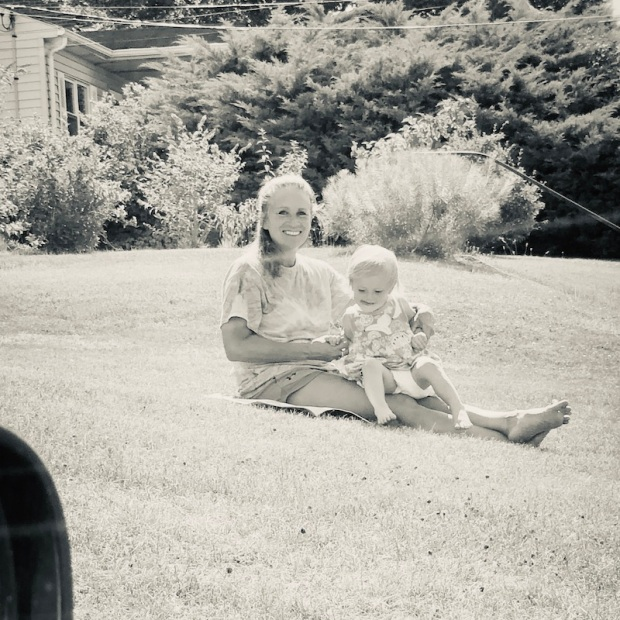Grandma and toddler sitting in grass