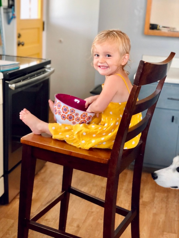 Toddler sitting in chair with yellow dress on and bowl in lap to help with cooking and baking