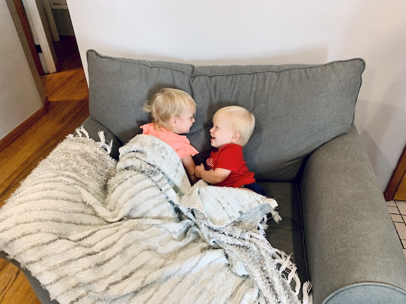 Toddler snuggling under blanket
