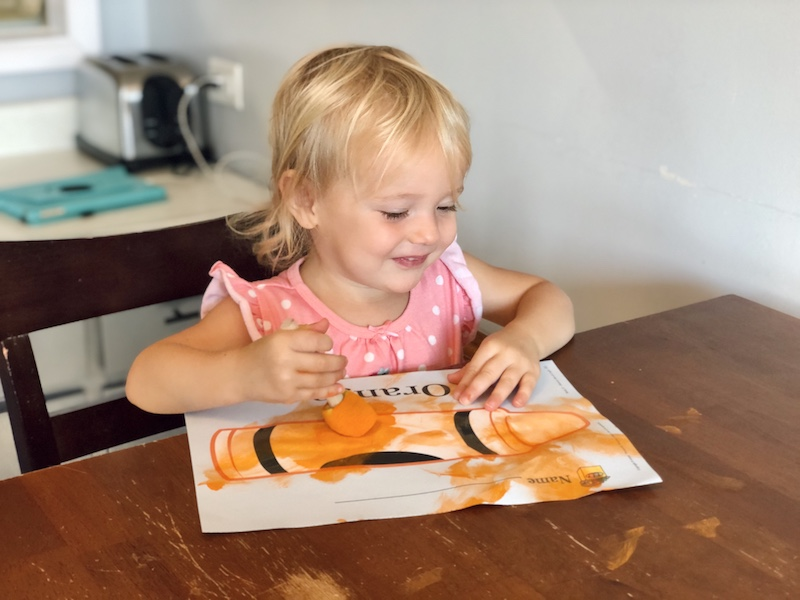 Toddler painting with orange paint