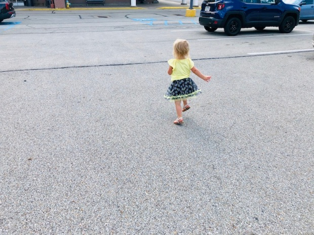 Toddler running through parking lot in black and yellow daisy skirt
