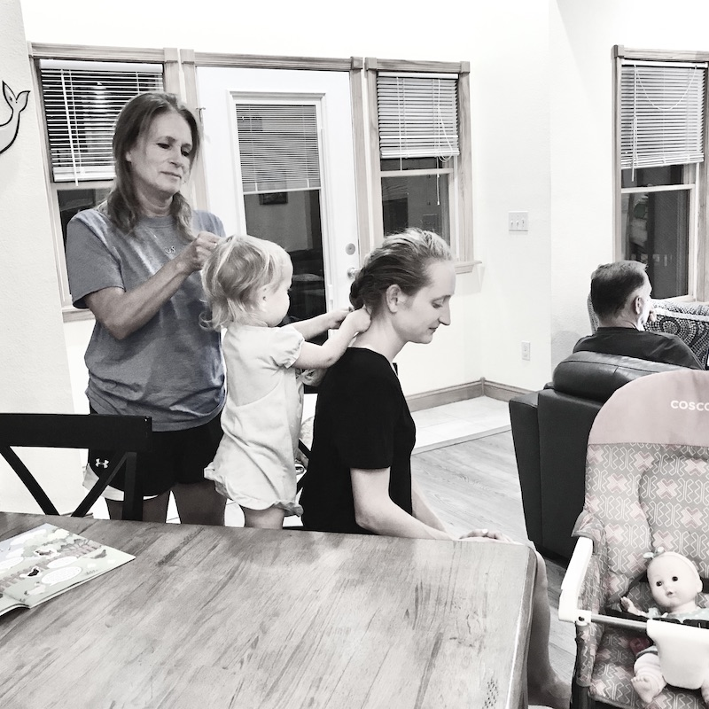 Three generations of women braiding hair