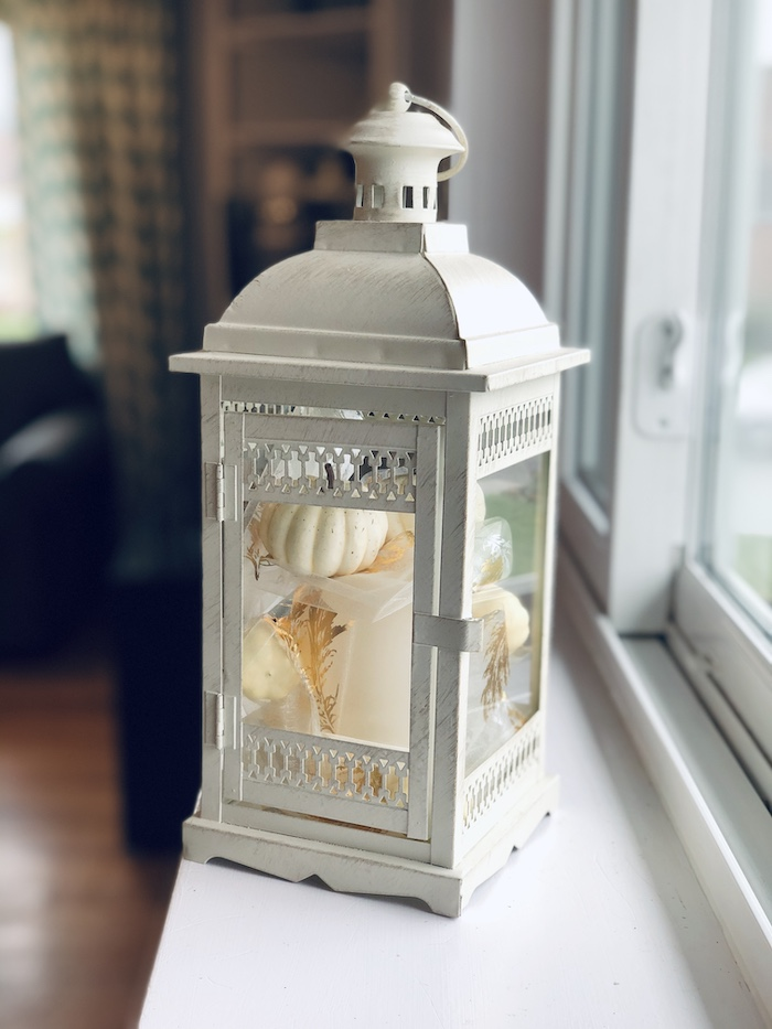 Fall lantern decorated in neutral colors with pumpkins and ribbon