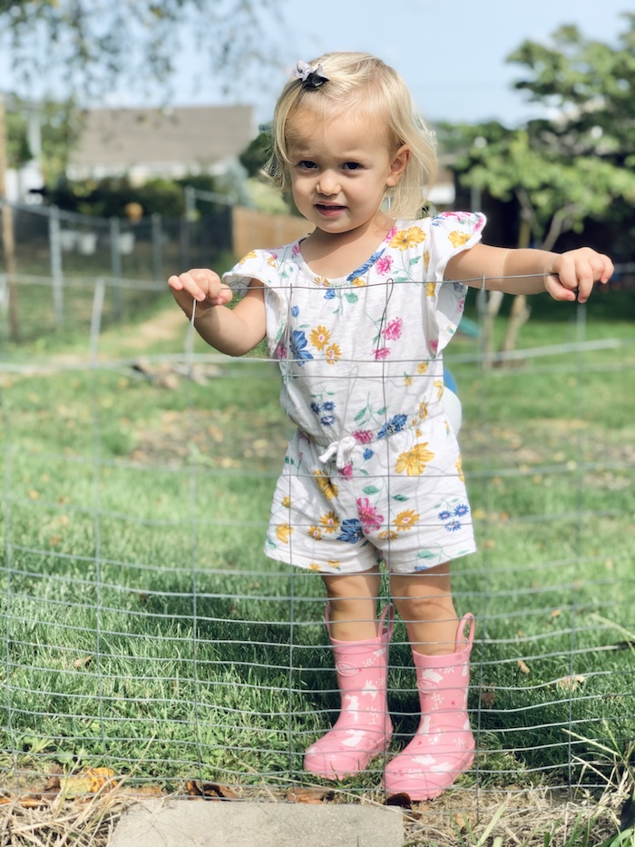 Toddler girl wearing romper and rain boots by garden