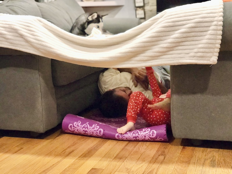 Dad and daughter inside couch and blanket fort
