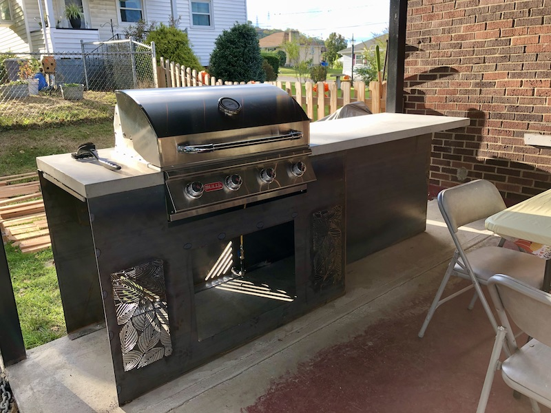 Outdoor kitchen with concrete countertops and built-in grill