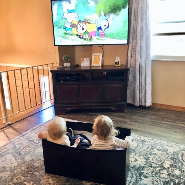 Toddlers sitting in a box watching TV