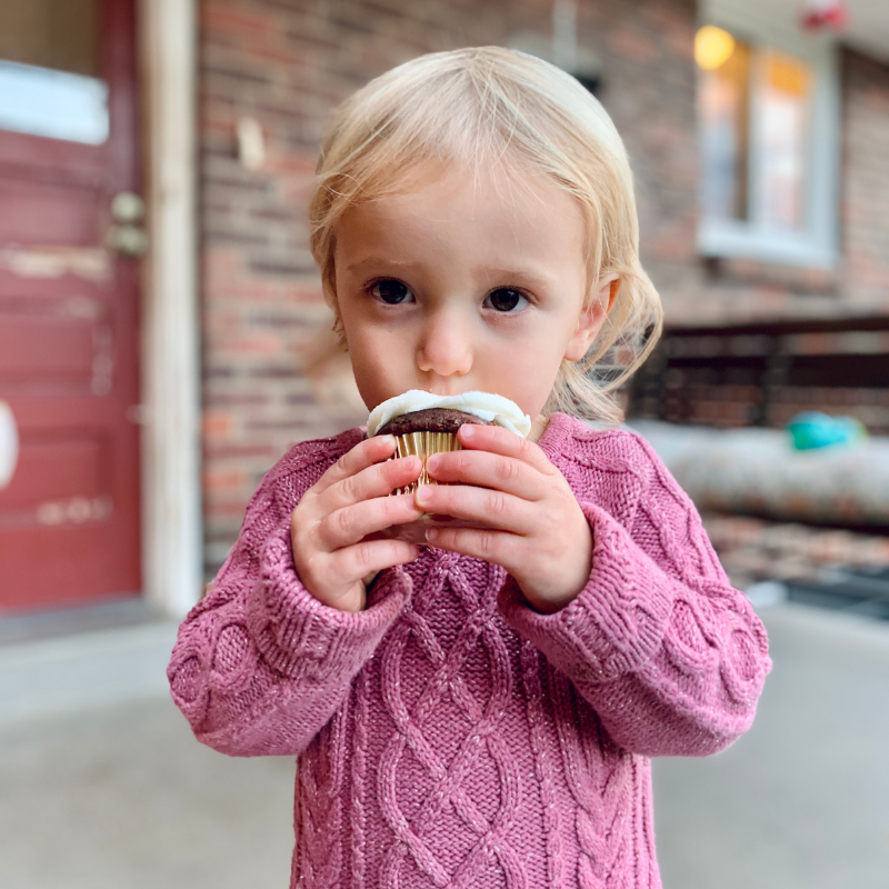 Toddler eating a cupcake