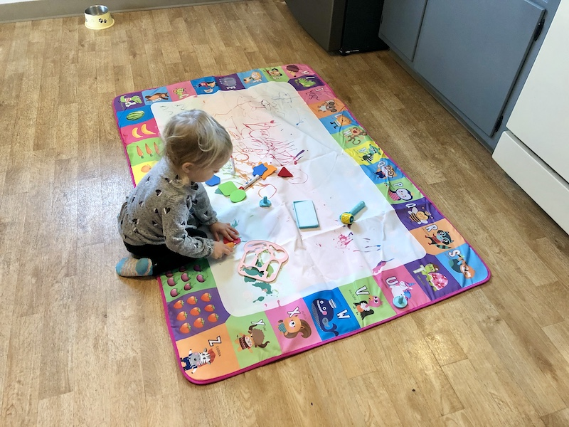 Toddler playing with water painting mat