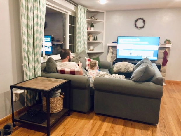 Dad and toddler watching TV with couches pushed together