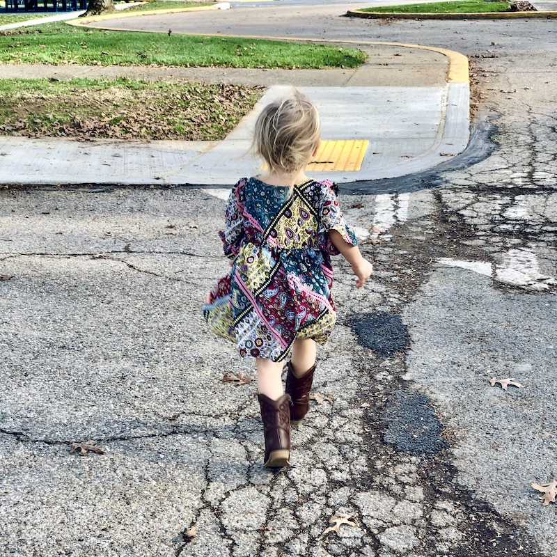 Toddler walking in dress and cowboy boots