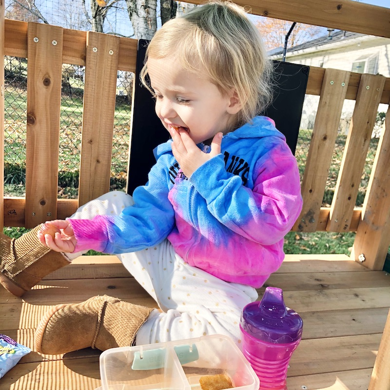 Toddler eating on top of swing set