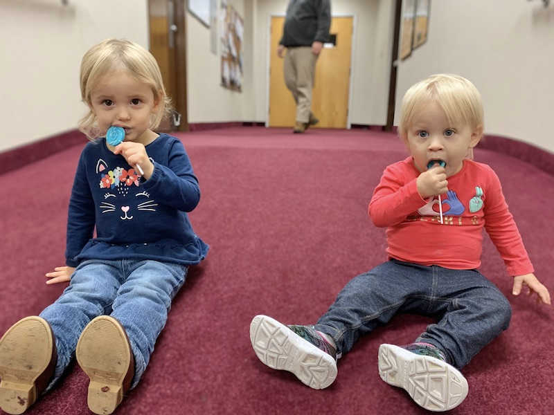 Toddlers eating lollipops