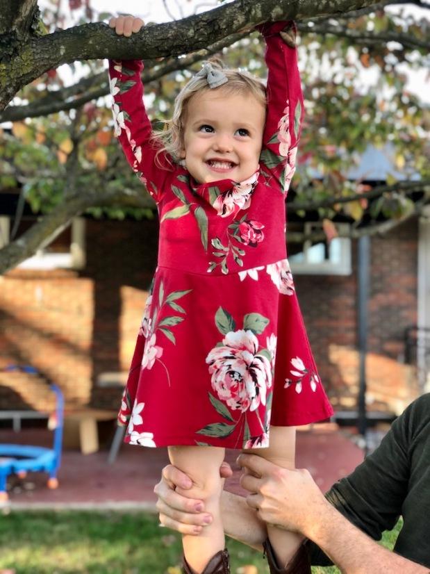 Toddler hanging in tree