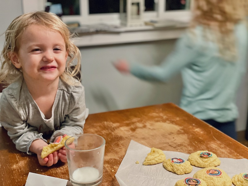 Girl eating Paw Patrol cookies
