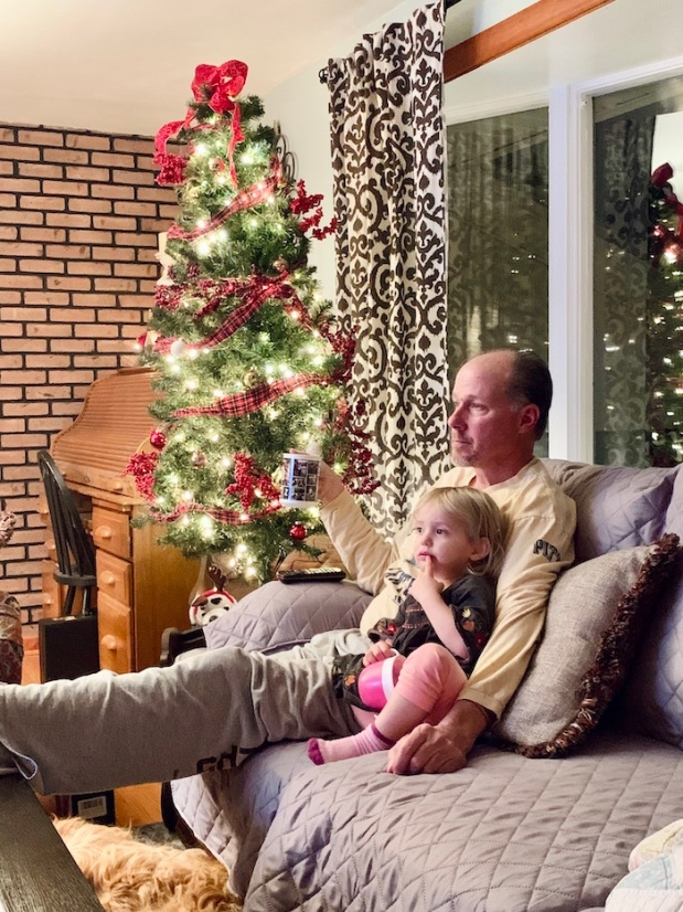 Grandpa with toddler at Christmas with tree
