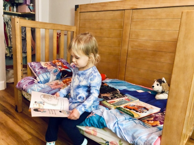Toddler reading on her bed
