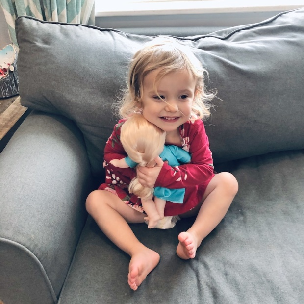 Girl hugging Frozen Elsa doll