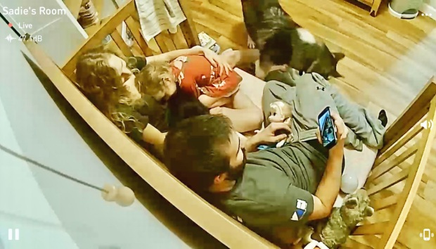 Family snuggling in toddler bed