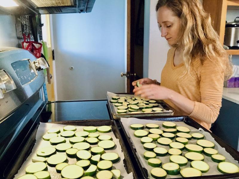 Girl cooking zucchini in kitchen