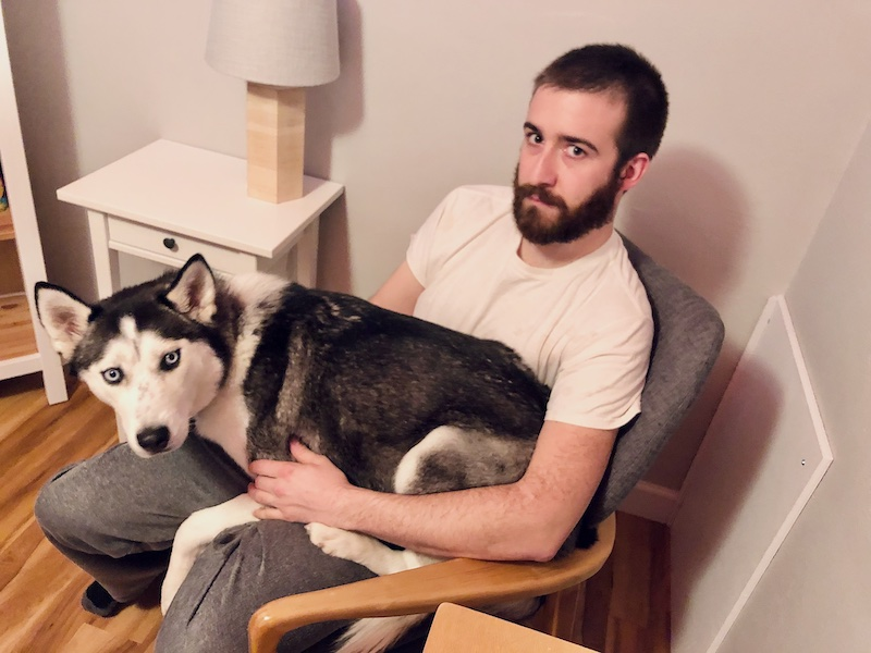 Guy holding husky in rocking chair