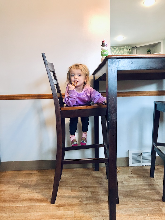 Toddler eating pretzels on the seat of a chair