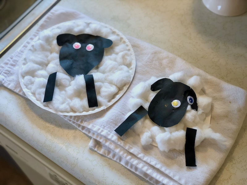 Toddler craft of making sheep with cotton balls and paper plates while homeschooling