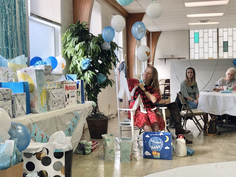 Opening gifts at baby shower for boy