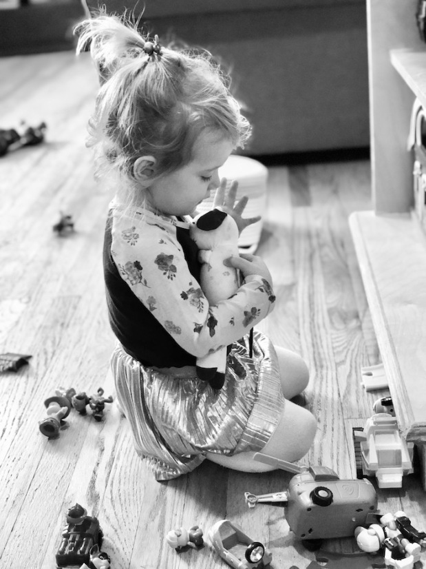 Black and white photo of toddler playing with stuffed animal